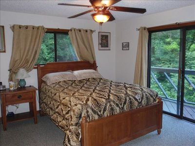 The master bedroom has access to the deck and a view of the falls