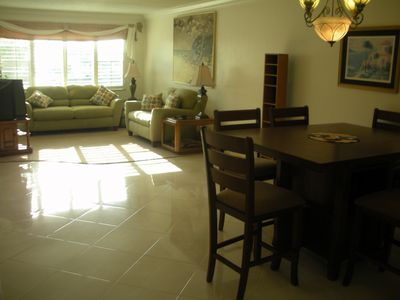 Spacious dining and living area, marble flooring, television, DVD, and sofa bed.