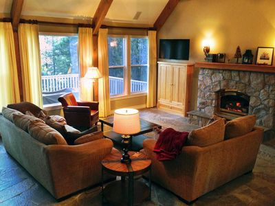 Main floor living room with flat screen TV, cozy fireplace, and stunning view