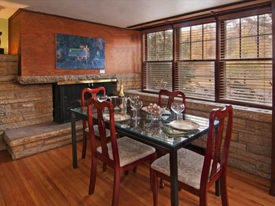 The dining room features a fireplace and a stone wall with windows