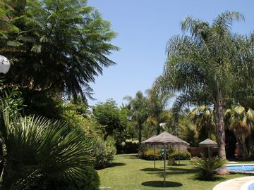 Lush well kept gardens and sun shades that surround the pool area