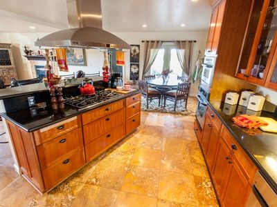 Kitchen & bistro nook w/granite counters, travertine floor & open to living room