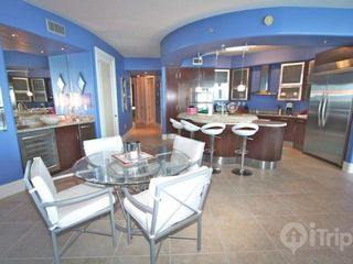 Orange Beach condo photo - Dining area with seating for four and four bar stools
