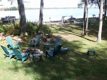 View of the firepit and swing near the lakefront. 100 ft. of sandy lakefront!