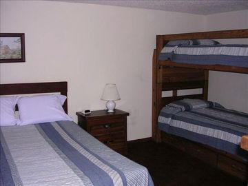 Bedroom with a queen bed and a set of bunkbeds.