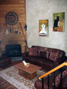 Living room with cathedral ceiling, leather sofas, wood floors, fire place.