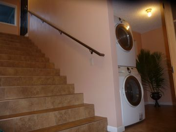 View of staircase and laundry area from entry door. H.E. Washer/dryer/basin.