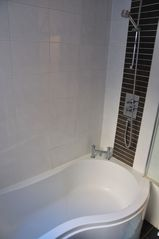 Greenwich apartment photo - Huge P shape bath with shower above.