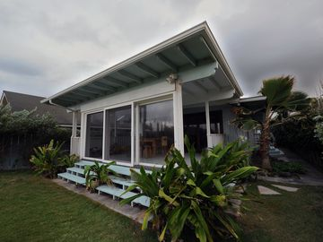 The porch is protected by sliding glass doors that open to the surf