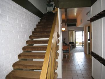 From the front door, stairs on the left.