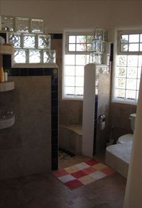 Bright, airy guest bathroom features travertine & talavera tile accents.
