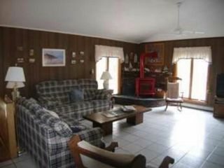 Living room w/2 ceiling fans, gas FP, TV and view to Bay - Eastham house vacation rental photo