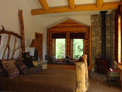 Master Suite Bedroom With Handcrafted Log Bed and  Pot Belly Stove