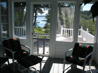 Screened in porch with door to the deck and the harbor beyond