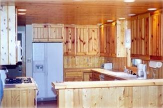 Charming knotty pine kitchen adjacent to large dining area.