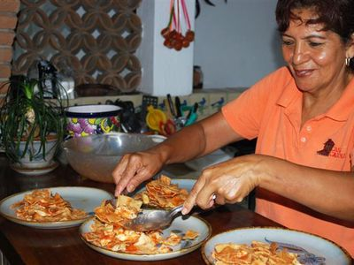 Chef Mari carefully serves chila quiles, one of her 12 breakfast entres.