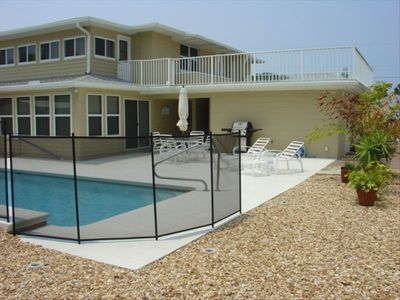 Private Pool area with patio recliner chairs and  BBQ grill and fenced backyard,