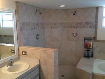 Large master bath features a dual Roman style shower with travertine tile