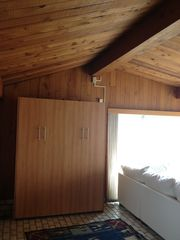 Yarmouth cottage photo - Queen wall bed folds out/up into cabinet in the living room, brand new mattress.