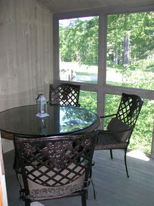 Lovely screened-in porch with dining set off one of the master bedrooms.