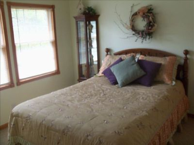 Nicely decorated bedroom with Queen size bed and a rear yard view.