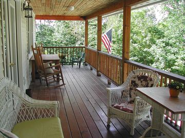 Covered balcony with table, rockers, and wicker chairs.