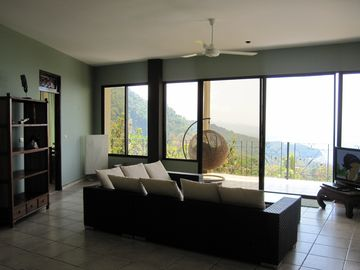 Ocean view & mountain view living room. TV has DVD and satellite TV.