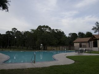 Panorama Village house photo - community pool with driving range in the background and pavillion on the right