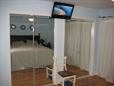 Master mirrors showing TV and King bed