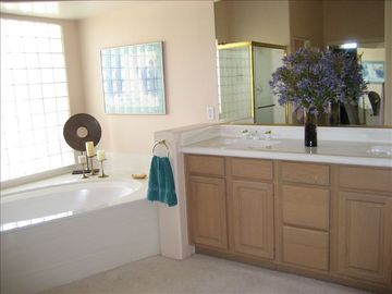 Master bedroom bathroom with double sinks, soaking tub, shower, make-up area.