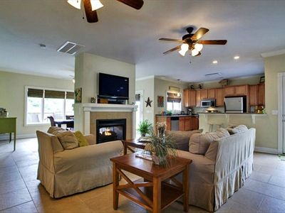 Family Room, dining room and kitchen with 2-sided fireplace and flat screen TV