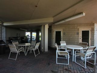 St Pete Beach condo photo - Covered patio on grounds with 2 gas bbqs and washrooms for the pool area (right)