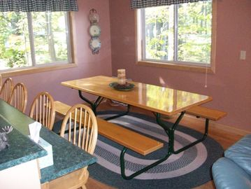 Dining area with picnic table and additional seating at left.