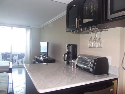 Counter Bar with 2 bar stools, microwave, silverware, dishes and fridge