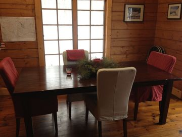 Dining table, kitchen to the left, double doors to the deck off to the right
