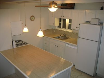 Large counter top with full sized stove, microwave, dishwasher, and refrigerator