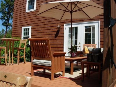 Cape Cod style cottage has a back deck created for relaxing in the sun.