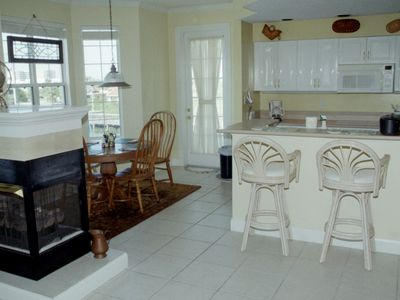 Breakfast nook, bar stools at kitchen bar, and door to second balcony