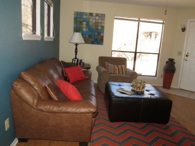 Comfortable leather couch faces the TV and window with mountain views.