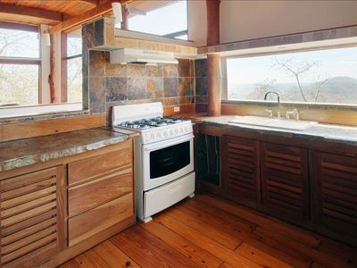 Even the kitchen has a breath-taking view of the ocean and green hills.