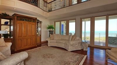Two story living room with view of covered porch