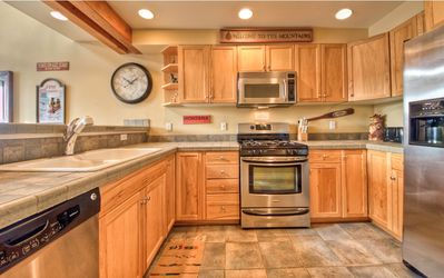 Stainless steel appliances with tile countertops and floors.