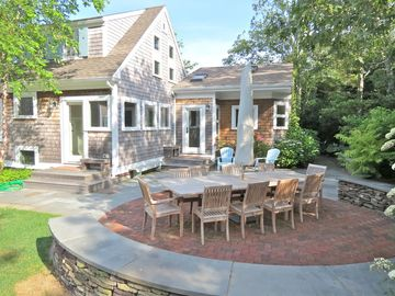 Relaxing private brick and bluestone patio houses an enormous teak dining table
