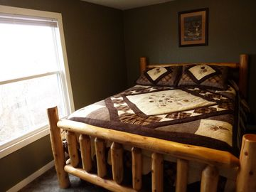 The second bedroom has a queen log bed