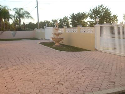 Gated Driveway with pavers and fountain. Plenty of room with covered parking