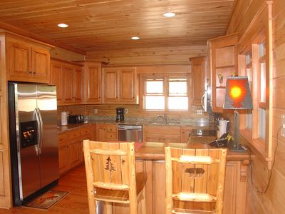 Kitchen with wood cabinets, granite and stainless appliances.