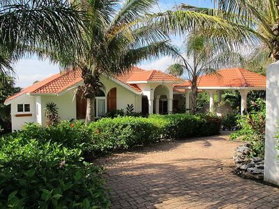 Front view of villa, lush landscaping, brick driveway and car port