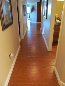 New wood floor tile installed in hallway, foyer, kitchen and bathrooms.