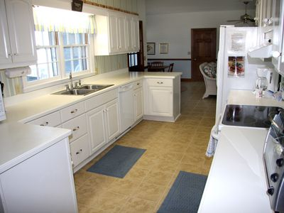 The kitchen has a full view of the screened porch, deck and beach.
