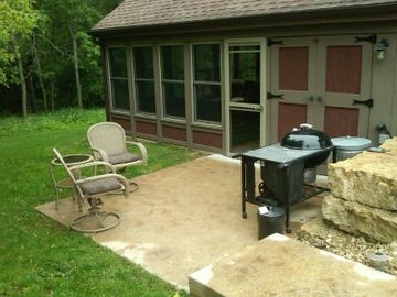 Side patio with grill and seating.